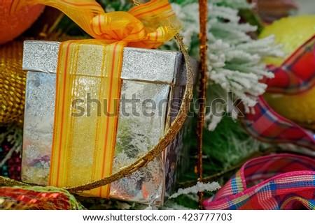 Box and ribbon Christmas tree ornament. Silver gift box and yellow-orange ribbon netting. Closeup view. - stock photo