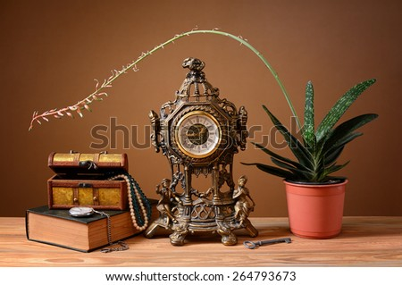 Box for jewelry, book clock and flowers on the table - stock photo