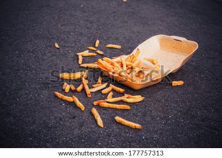 Box of chips spilled all over on the ground - stock photo