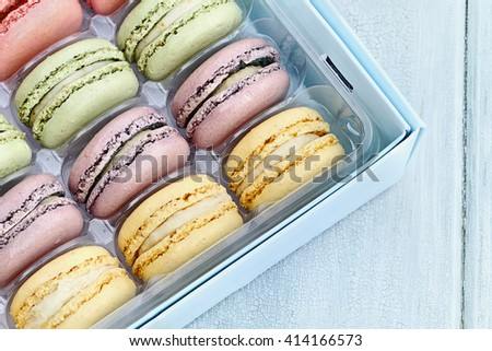 Box of fresh pastel colored macarons shot from overhead. - stock photo