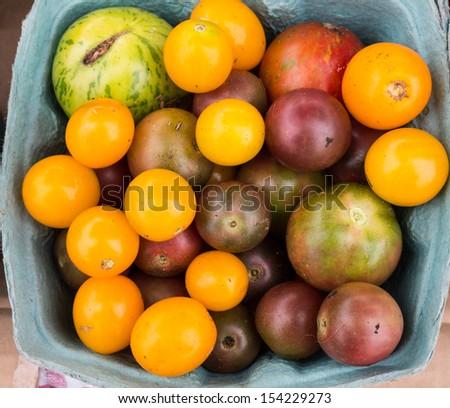 Box of heirloom tomatoes at local farm market.  - stock photo