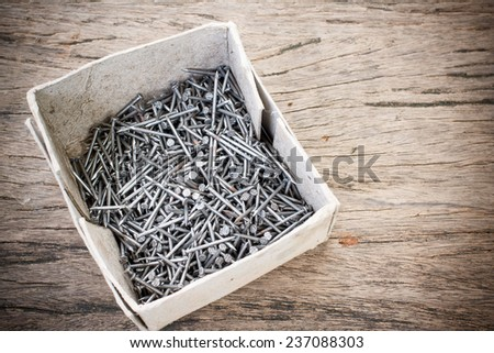 Box of old metal nails on wood background - stock photo