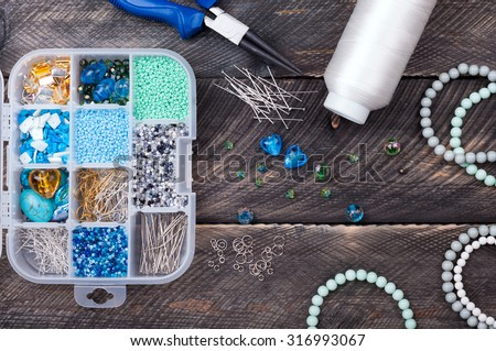 Box with beads and pins, spool of thread, plier and glass hearts to create hand made jewelry on old wooden background. Handmade accessories. Top view - stock photo