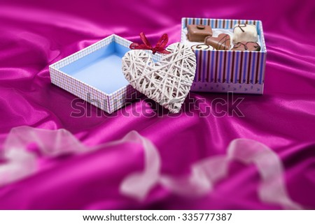 Box with chocolates candies and heart on satin pink background - stock photo