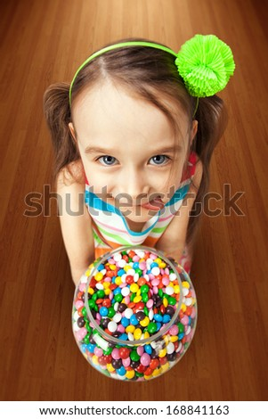 Box with colorful candies in the hands of little girl - stock photo