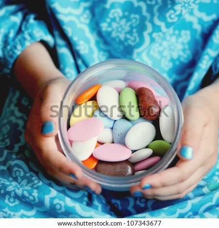 Box with colorful candies in the hands of little girl, focus on candies - stock photo
