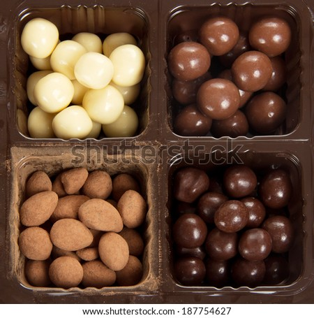Box with different round candies - stock photo