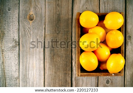 Box with lemons on a wooden background. - stock photo