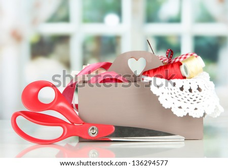 Box with the materials at hand sewing on bright background - stock photo