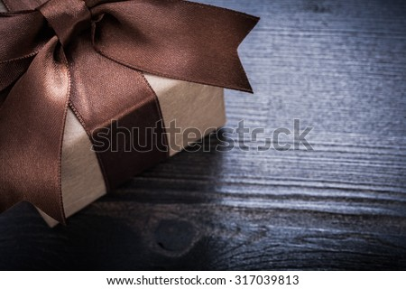 Boxed present with tied bow on vintage wooden surface. - stock photo