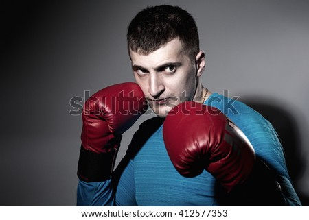 Boxer in red gloves on a black background - stock photo