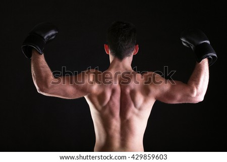 Boxer raising his arms strong athletic muscle man, sports guy showing his muscles male back isolated on black background - stock photo