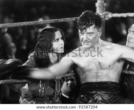 Boxer sitting in the corner of a boxing ring - stock photo