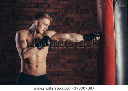 Boxer training on a punching bag in the gym. - stock photo