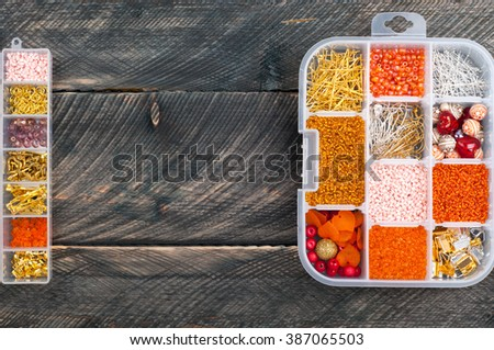 Boxes with beads and accessories to create handmade jewelry on old wooden background. Copy space. Top view - stock photo