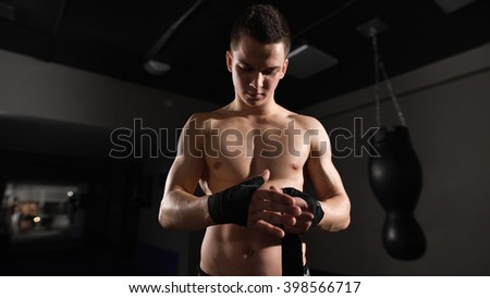 Boxing bandage. Close up of a sportsman binding red boxing bandage in a gym. Dark area - stock photo