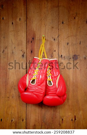 Boxing-glove hanging on wooden background - stock photo