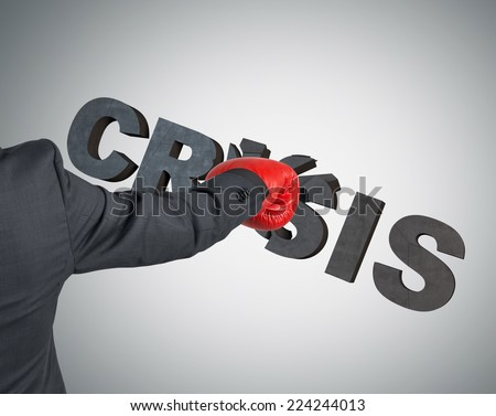 Boxing glove punching the word 'crisis'. A metaphor of to deal with crisis. - stock photo