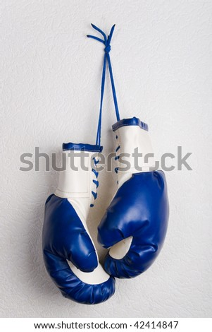Boxing gloves hanging on a white wall - stock photo