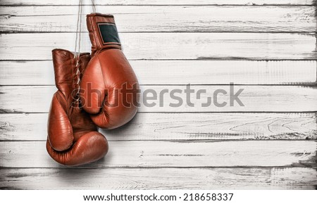 Boxing gloves hanging on wooden wall - stock photo