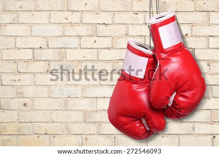 Boxing gloves over brick wall background - stock photo