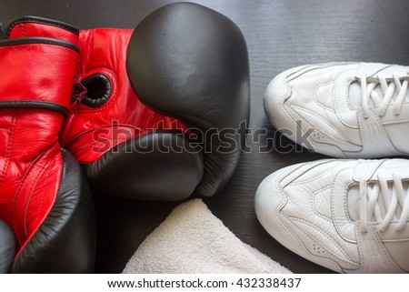 Boxing shoes, gloves and towel on black background - stock photo
