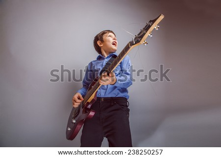 boy adolescence European appearance sings and plays guitar - stock photo