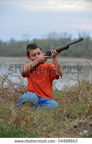 Boy aiming rifle upwards - stock photo