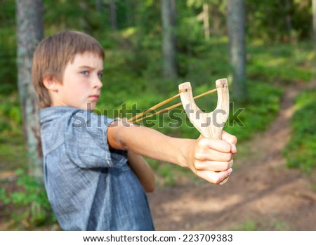 Boy aiming wooden slingshot outdoors - stock photo