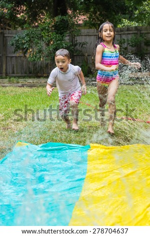 Boy and a girl playing in sprinklers outside - stock photo