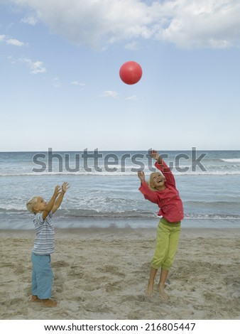 Boy and a girl playing with a ball on the beach - stock photo
