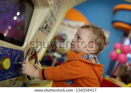Boy and amusement car at indoor playground - stock photo