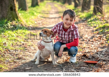 boy and dog walking in park - stock photo