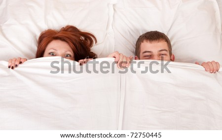 boy and girl are hiding under the blanket. - stock photo