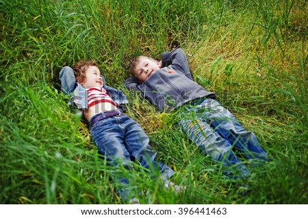 Boy and girl are resting on the green grass in summer. Happy children, kids, brother and sister, friends lying on grass on picnic on the nature. Funny kids relax, play outdoors in park. Top view. - stock photo