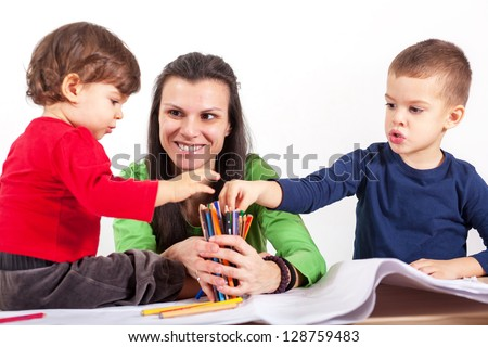 Boy and girl choosing crayons which mom is holding in hands - stock photo