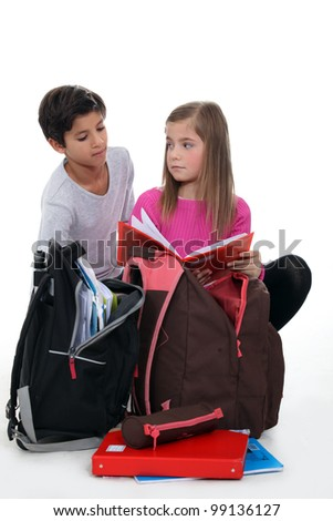 boy and girl doing their homework after school - stock photo
