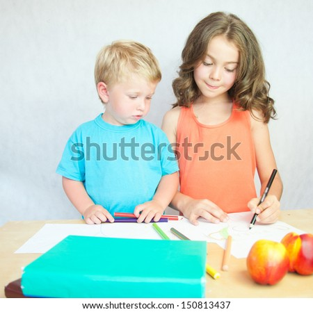 Boy and girl drawing with colourful pencils. - stock photo