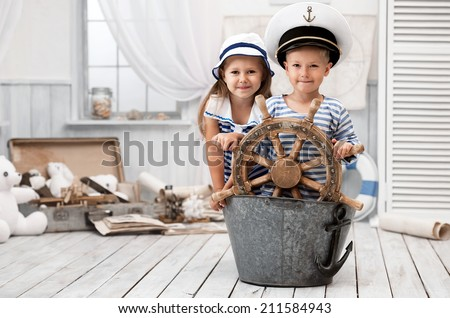 Boy and girl dressed as a captain and sailors played on the ship out of the bath in his room - stock photo