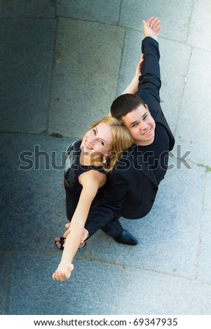Boy and girl dressed in black looking up. Stand back to back outstretched hands. - stock photo