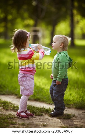 boy and girl drinking mineral water in park - stock photo