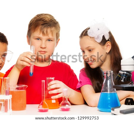 Boy and girl experimenting with chemistry mixing liquids - stock photo