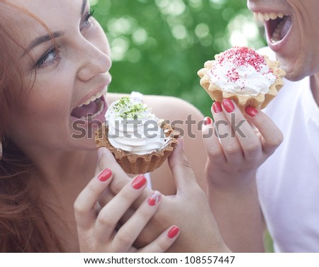 boy and girl feed each other delicious sweet cakes outdoors at a picnic - stock photo