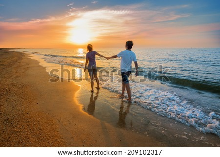 Boy and girl go on the beach during sunset - stock photo