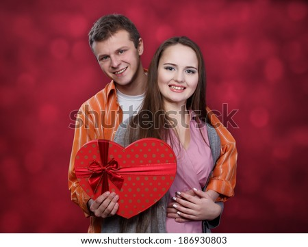 Boy and girl hold box in a shape of heart at right background - stock photo