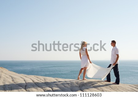 Boy and girl holding a white shawl standing on a rock and look at each other - stock photo