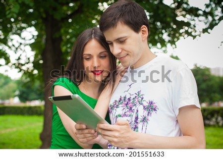boy and girl in green dress holding tablet together outdoor in the park  - stock photo