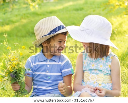 Boy and girl in hats looking at each other - stock photo