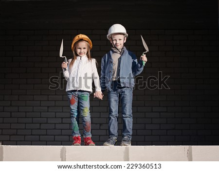 boy and girl in helmets build house - stock photo