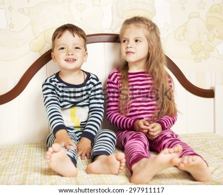 boy and girl in pajamas on bed - stock photo